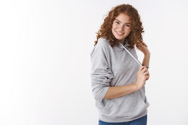Studio strzał bezczelny wesoły rudowłosy charyzmatyczna młoda dziewczyna w szarej bluzie z kapturem uśmiechnięta głupio flirtująca chichocząca gra we włosach w szarej casualowej bluzie z kapturem, stojąca na białym tle rozbawiona szczęściarz
