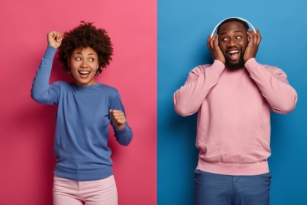 Studio strzał beztroskiej emocjonalnej etnicznej kobiety i mężczyzny tańczy w rytmie głośnej muzyki, mają optymistyczny nastrój, ubrani w codzienne ubrania