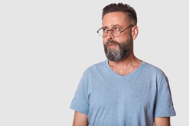 Studio strzał młodego brodatego mężczyzny atrakcyjnego z brodą, noszącego zwykłe gówno i okulary, wygląda ciekawie na bok