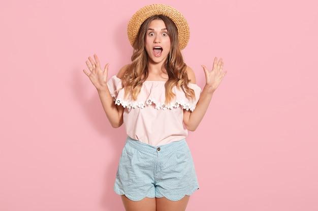 Studio strzał młodej kobiety na sobie różową letnią bluzkę, niebieskie krótkie, okulary przeciwsłoneczne i letni kapelusz stojący z otwartymi ustami w szoku, wygląda na zaskoczonego, wyrażając zdziwienie. koncepcja ludzi i emocji.