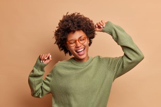 Studio strzał młodej kobiety tańczy beztrosko, dobrze się bawi, podnosi ramiona, czuje się zrelaksowany, nosi przezroczyste okulary i sweter casul odizolowany na brązowej ścianie