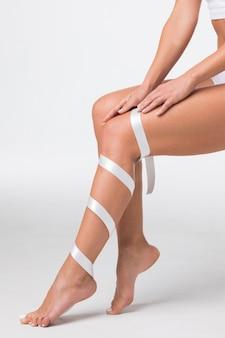 Studio strzał młodej kobiety z idealnym ciałem z nogą owiniętą białą wstążką, depilacja, koncepcja żylaków