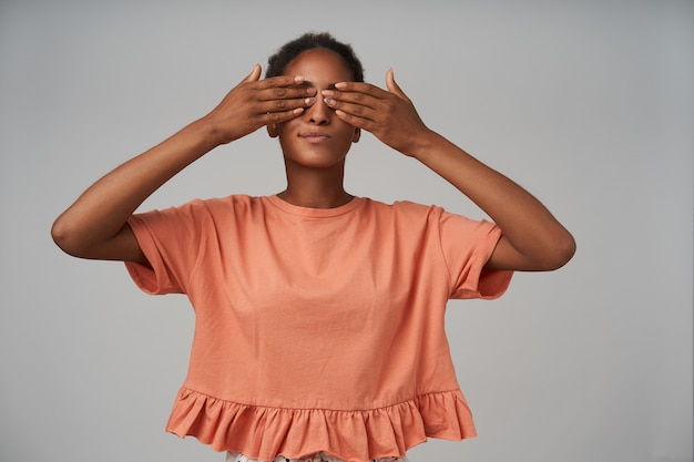 Studio strzał młodych całkiem brązowowłosych kobiet ubranych w różową bluzkę zasłaniając oczy z podniesionymi dłońmi, stojąc nad szarą ścianą