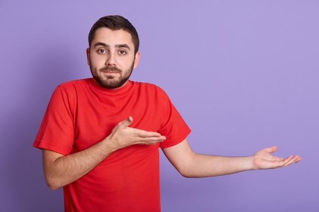Studio strzał niezadowolony mężczyzna ubrany w czerwoną koszulkę na co dzień.