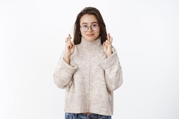 Studio strzał optymistycznej szczęśliwej i zachwyconej młodej kobiety w okularach i swetrze ze skrzyżowanymi palcami na szczęście, uśmiechając się z nadzieją, oczekując spełnienia cudu, życząc i modląc się nad szarą ścianą.