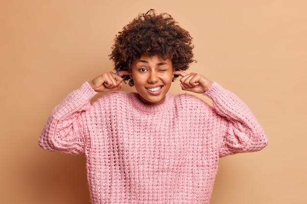 Studio strzał pięknej kobiety zaciska zęby zatykając uszy, aby uniknąć głośnego hałasu, prosi o zatrzymanie głośnego dźwięku, nosi dzianinowy sweter odizolowany na beżowej ścianie