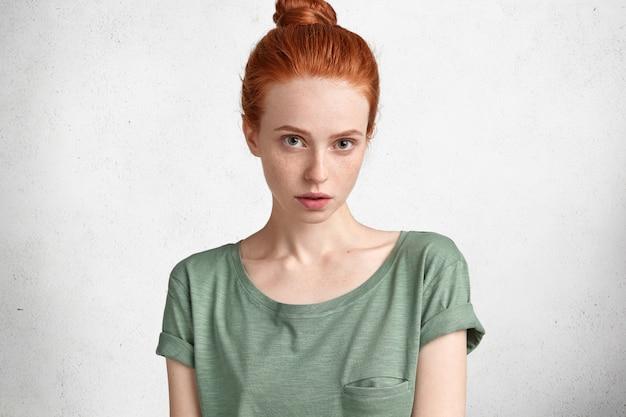 Studio strzał pięknej rudowłosej kobiety o zdrowej, piegowatej skórze, ubrana niedbale, ma poważny wyraz twarzy, odizolowane na białym betonowym murem.