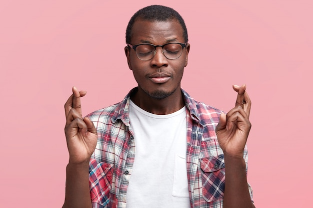 Studio strzał pożądanego młodego mężczyzny z ameryki południowej, trzymającego kciuki i zamknięte oczy, ubranego w swobodną kraciastą koszulę, który ma nadzieję na awans w pracy lub otrzymanie pracy