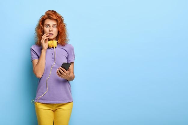 Studio strzał przerażonej kobiety tysiącletniej z falistymi rudymi włosami, pozowanie na niebieskiej ścianie