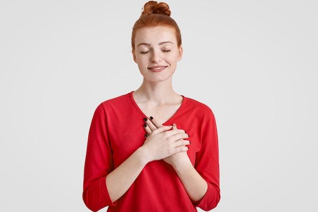 Studio strzał spokojnej nieostrożnej kobiety z imbirową koką do włosów, trzyma obie dłonie na piersi, zamyka oczy, ubrany w czerwony sweter, na białym tle, wyraża wdzięczność i przyjazne uczucia