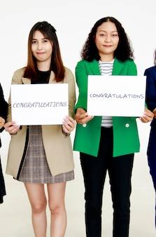 Studio strzał szczęśliwej uśmiechniętej kobiecej kadry oficerskiej i współpracowników w biznesie nosi stojące spojrzenie na aparat trzymający gratulacje papierowy znak dla nowego pracownika pokaż ciepłe powitanie dla nowego przybysza.