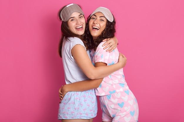 Studio strzał uśmiechniętych uroczych kobiet z maskami do spania, ubranych w piżamę, stojących targujących się na tle różanego studia, panie targujące się nawzajem, wyrażających szczęście. koncepcja przyjaźni.
