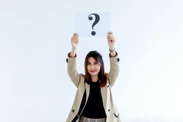 Studio strzał wątpliwych żeńskich pracowników oficera w garniturze spojrzeć na aparat trzymając znak zapytania papier kartonowy znak podnieść narzut pokazując ciekawość myślenia odpowiedzi na białym tle.