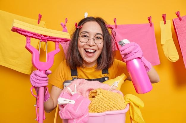 Studio strzał wesołej azjatki patrzy szczęśliwie na aparat lubi wykańczać prace domowe, trzyma detergent do czyszczenia, a mop robi porządki na linie z suszeniem ubrań. codzienna rutyna