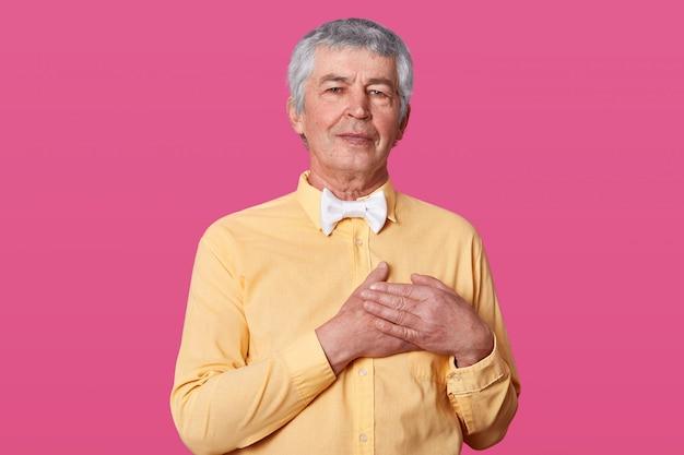 Studio strzał z przyjemnie wyglądającym sercem starszego mężczyzny trzyma ręce na piersi