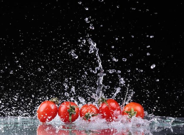 Studio strzał z zamrozić ruch pomidory czereśniowe w plusk wody na czarnym tle