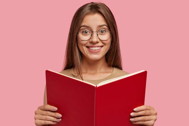 Studio strzał zadowolonej, wesołej kobiety ma spokojny, spokojny, szczęśliwy wyraz, trzyma otwarty podręcznik z przodu
