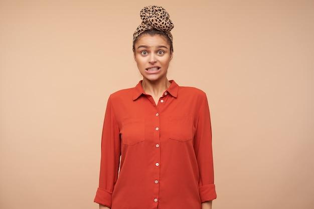Studio strzał zdezorientowanej młodej brązowowłosej kobiety wykręcającej usta, patrząc zaskoczony z przodu, pozując na beżowej ścianie w zwykłych ubraniach
