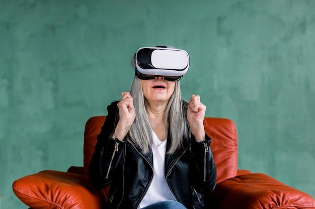 Studio strzał zdziwionej, ładnej, starszej kobiety o siwych włosach, ubranej w stylową skórzaną kurtkę, siedzącej w czerwonym miękkim fotelu w specjalnych 3d wirtualnych okularach