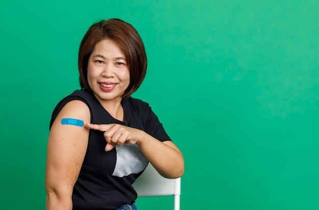 Studio strzałów azjatyckiej kobiety w średnim wieku, siedzącej z uśmiechem i pokazującej niebieski bandaż gipsowy na ramieniu po otrzymaniu szczepienia przeciwko koronawirusowi covid 19 przez lekarza w klinice na zielonym tle.