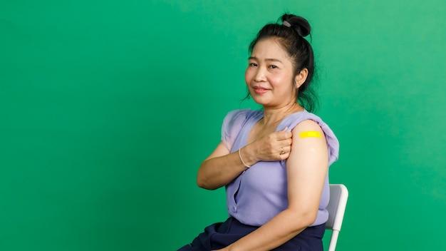 Studio strzałów azjatyckiej kobiety w średnim wieku, siedzącej z uśmiechem i pokazującej żółty gipsowy bandaż na ramieniu po otrzymaniu szczepienia przeciwko koronawirusowi covid 19 przez lekarza w klinice na zielonym tle.