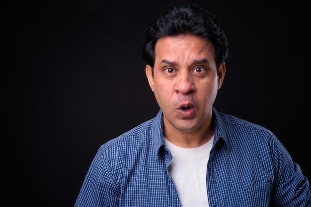 Studio strzałów dojrzałego przystojnego mężczyzny indyjskiego na czarnym tle