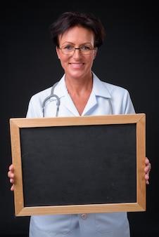 Studio strzałów dojrzałej pięknej kobiety skandynawskiej lekarza z krótkimi włosami na czarnym tle