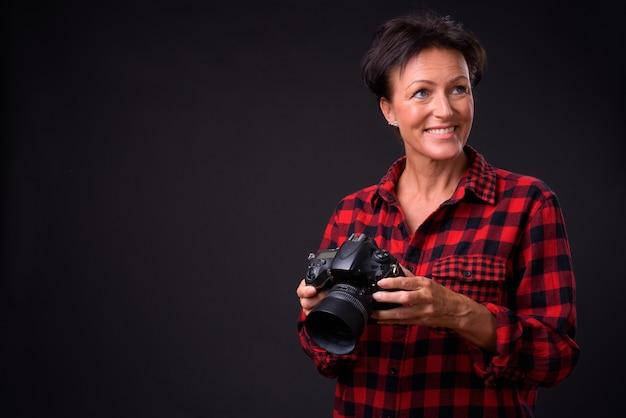 Studio strzałów dojrzałej pięknej skandynawskiej kobiety z krótkimi włosami na czarnym tle