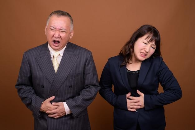 Studio strzałów dojrzałych japońskich biznesmenów i dojrzałych japońskich biznesmenów razem na brązowym tle