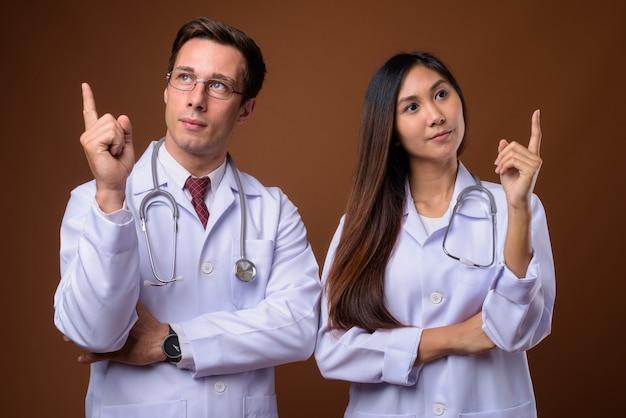 Studio strzałów dwóch młodych lekarzy razem przeciwko brązowemu backgrou