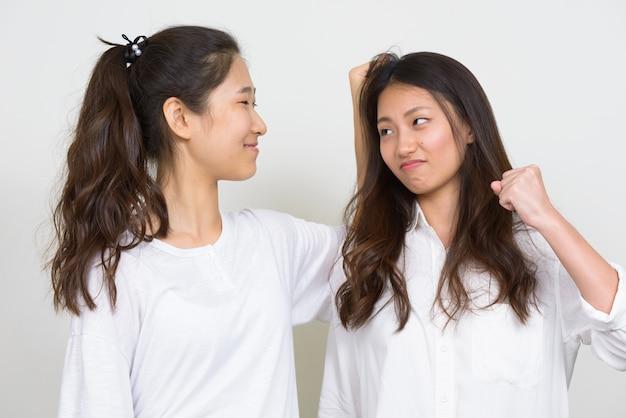 Studio strzałów dwóch młodych pięknych koreańskich kobiet jako przyjaciół razem na białym tle