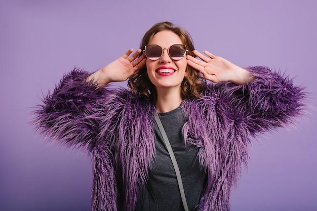 Studio strzałów fascynującej młodej kobiety z krótkimi włosami, śmiejąc się na fioletowym tle