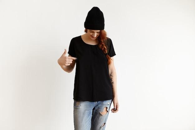 Studio strzałów kaukaski dziewczyna w stylowy kapelusz i poszarpane niebieskie dżinsy, patrząc w dół i wskazując palcem wskazującym