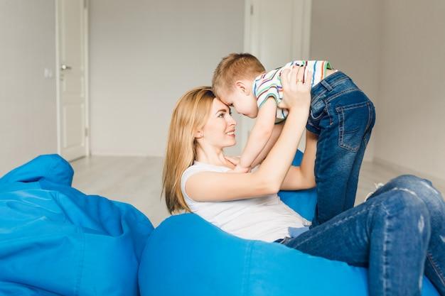 Studio strzałów matki bawiące się z dzieckiem. mama trzyma chłopca w ramionach