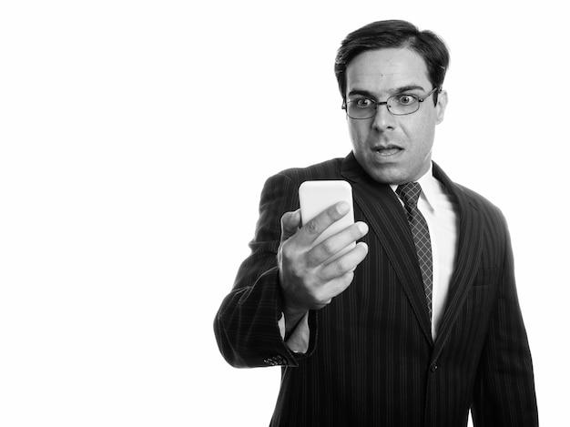 Studio strzałów młodego biznesmena perskiego przy użyciu telefonu komórkowego, patrząc zszokowany na białym tle