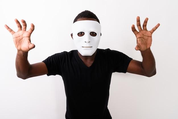 Studio strzałów młodego czarnego mężczyzny afrykańskiego noszenie maski i pokazywanie