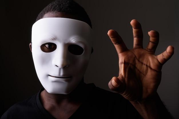 Studio strzałów młodego czarnego mężczyzny afrykańskiego w ciemnym pokoju noszenie maski