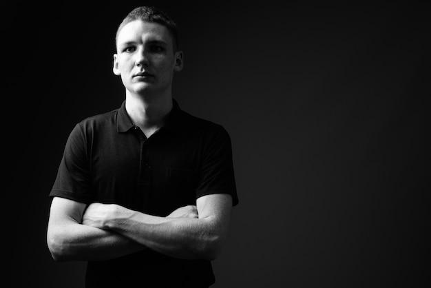 Studio strzałów młodego człowieka na czarnym tle w czerni i bieli