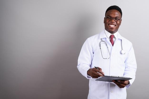 Studio strzałów młodego lekarza afrykańskiego człowieka w okularach, trzymając schowek na białym tle