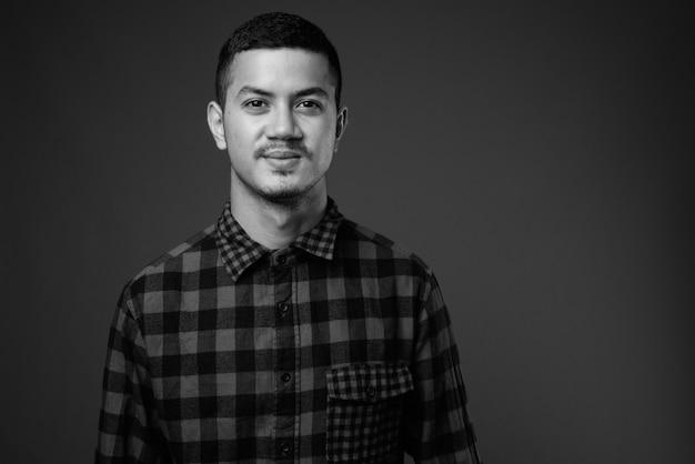 Studio strzałów młodego mężczyzny wieloetnicznego azji na sobie koszulę w kratkę przed szarej ścianie w czerni i bieli