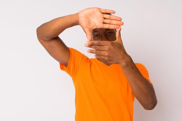 Studio strzałów młodego przystojnego mężczyzny afrykańskiego z włosami afro na białym tle