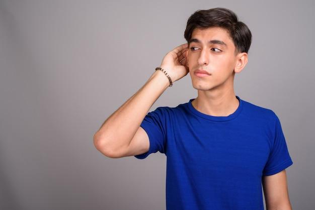 Studio strzałów młodego przystojnego nastoletniego perskiego chłopca na szarym tle