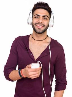 Studio strzałów młodego szczęśliwego człowieka indyjskiego słuchania muzyki