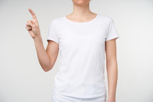 Studio strzałów młodej kobiety o jasnej karnacji pokazując literę z podniesioną ręką podczas nauki alfabetu głuchych, będąc odizolowane na białym tle