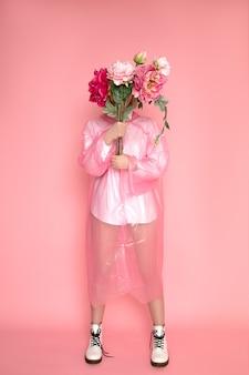 Studio strzałów młodej kobiety z bukietem kwiatów piwonii przed jej twarzą.