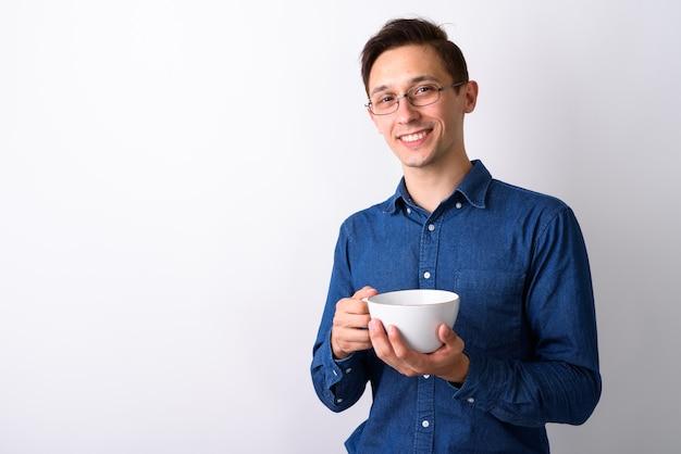 Studio strzałów młody człowiek szczęśliwy, uśmiechając się i trzymając kubek kawy wh
