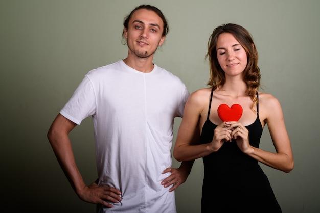 Studio strzałów młody przystojny mężczyzna i młoda kobieta piękne razem na kolorowym tle