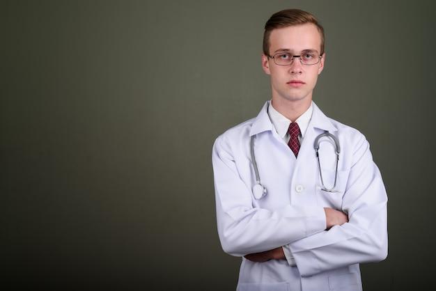 Studio strzałów młody przystojny mężczyzna lekarz noszenie okularów na kolorowym tle