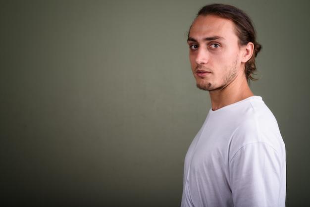 Studio strzałów młody przystojny mężczyzna ubrany w białą koszulę na kolorowym tle