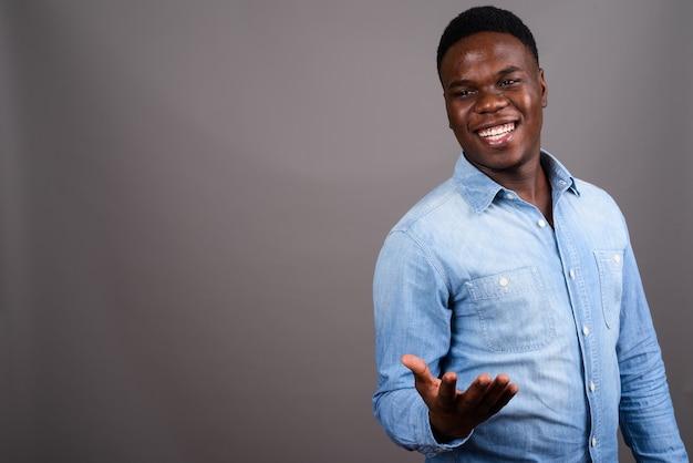 Studio strzałów młodych afrykańskich człowieka na sobie dżinsową koszulę na szarym tle